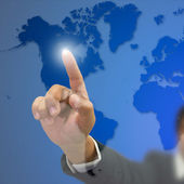 Right hand Businessman index press on world map — Stock Photo