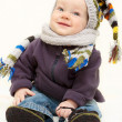 Cute baby boy in knitted handmade hat, scarf and bootees is sitt — Stock Photo