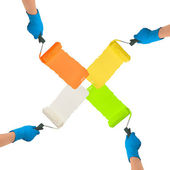 Hands with rollers dipped in bright colors paint each other trac — Stock Photo