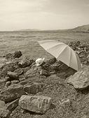 Zomer hoed en een paraplu op een stenen strand — Stockfoto