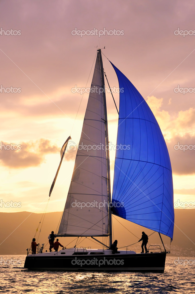 Sail boat against sun with unrecognizable  Stock Photo #7114452