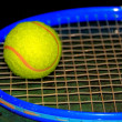 Tennis ball and racket on green background — Stock Photo