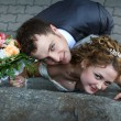 Bride and groom near a wall — Stock Photo