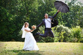 Bride and groom flying on umbrella — Stock Photo