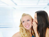 Two beautiful women telling secret — Stock Photo