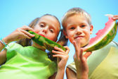 Young girl and boy eating watermelon — Stock Photo