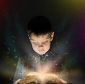 Boy is reading a magic book — Stock Photo