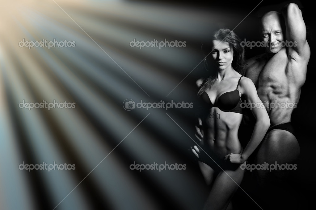 Bodybuilding. Strong man and a woman posing on a black background — Stock Photo #7898841