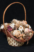Bouquet of withered flowers in a wicker basket — Stock Photo