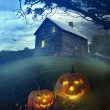 Halloween pumpkins in front of Spooky house - Stock Photo