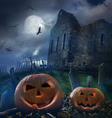 Pumpkins in graveyard with church ruins — Stock Photo