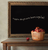 Fresh apples on wooden table with blackboard — Stock Photo