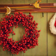 Red wreath with Santa hat hanging on rustic wall — Stock Photo