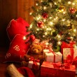 Brightly lit Christmas tree with gifts — Stock Photo