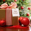 Christmas gift sitting on a table — Stockfoto