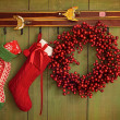 Christmas stockings and wreath hanging on  wall - Stock Photo
