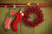 Christmas stockings and wreath hanging on wall — Stockfoto