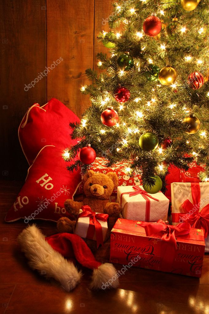 Closeup of brightly lit Christmas tree with gifts — Stock Photo #7371220