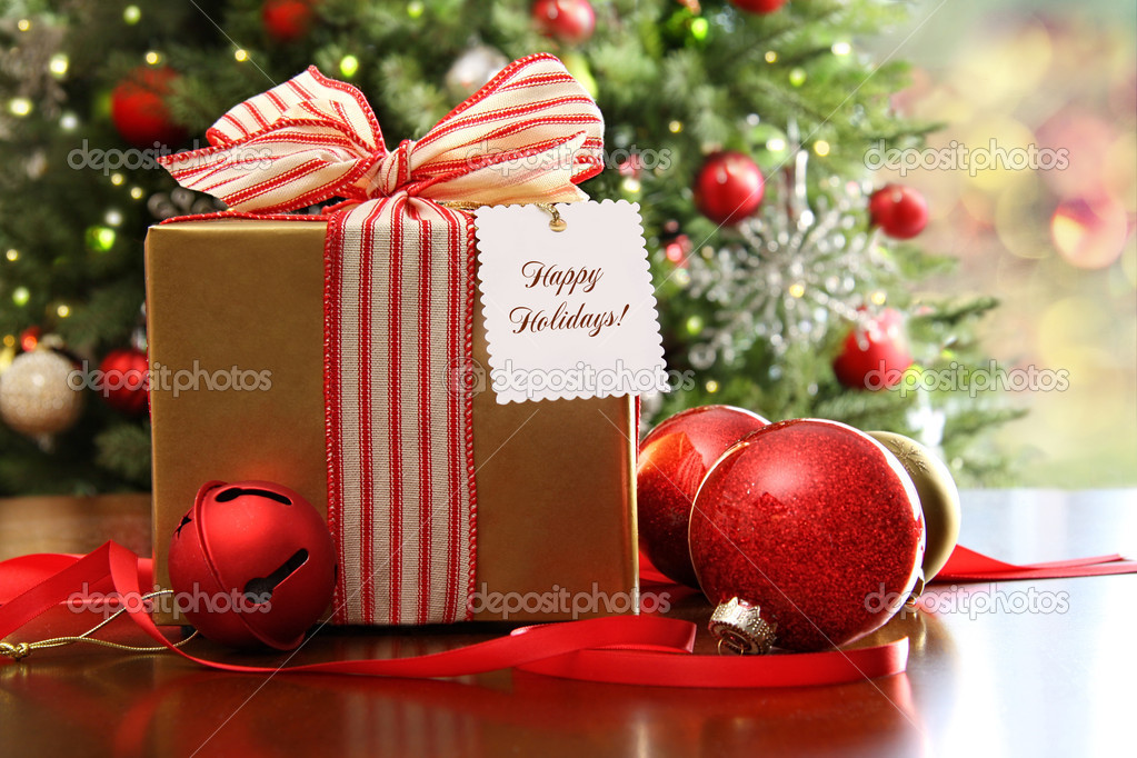 Christmas gift sitting on a table with a tree in the background  Foto Stock #7371237