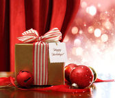 Gold Christmas gift box and ornaments with sparkle lights — Zdjęcie stockowe