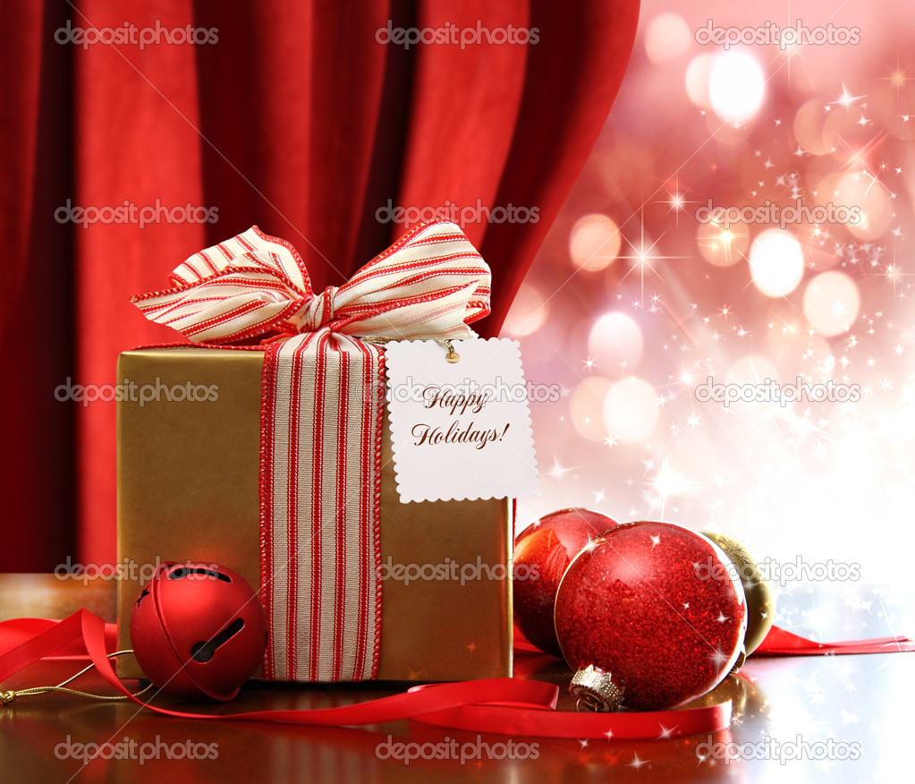 Gold Christmas gift box and ornaments with sparkle lights in background — Foto Stock #7523308