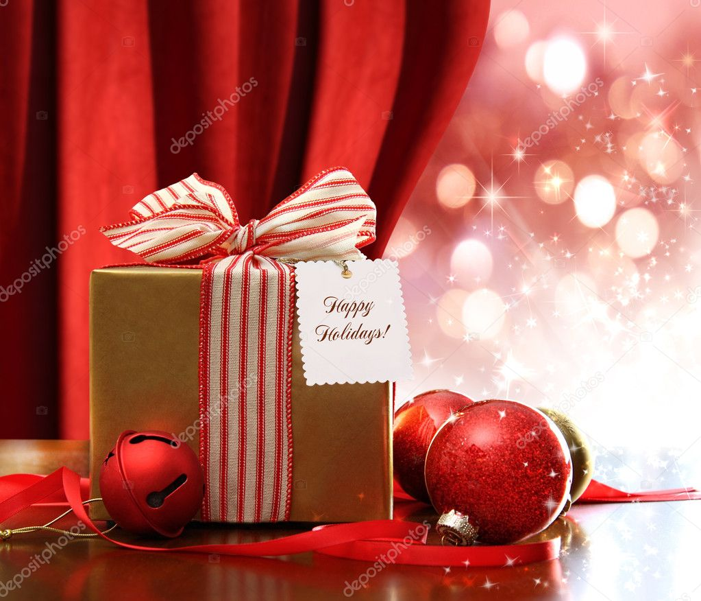 Gold Christmas gift box and ornaments with sparkle lights in background — Stockfoto #7523308