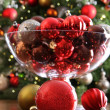 Christmas ornaments on table in front of tree — Stock Photo