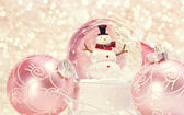 Snow globe with pink ornaments — Stock Photo