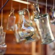 Decanters of bohemian glass hanging on hooks — Stock Photo