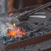 Embers, fire, smoke and blacksmith tools — Stock Photo