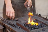 Embers, fire, smoke, tools and the hands of a blacksmith — Foto de Stock