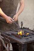 Embers, fire, smoke, tools and the hands of a blacksmith — Stock Photo