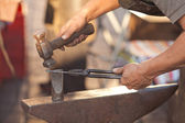 Hammer, anvil and the hands of a blacksmith — Stock Photo
