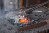 Embers, fire, smoke and blacksmith tools — Stock Photo