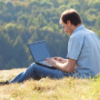 Young man using laptop sitting on the grass on the hillside — Stock Photo #7312559