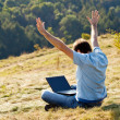 Young man using laptop sitting on the grass on the hillside — Stock Photo #7312602