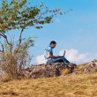 Young man using laptop sitting on a hill against the blue sky — Stock Photo