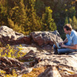 Young man using laptop sitting on a rock slope — Stock Photo #7312844