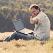 Stock Photo: Young musing laptop sitting on grass on hillside