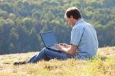 Hillside çimlere oturup dizüstü kullanan genç adam — Stok fotoğraf