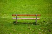 Banco solitario sobre fondo verde hierba — Foto de Stock