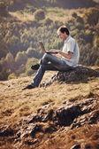 Jonge man met behulp van laptop zittend op het gras op de heuvel — Stockfoto