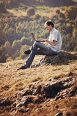 Young man using laptop sitting on the grass on the hillside — Stock Photo