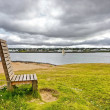 Wooden bench on a river — Stock Photo