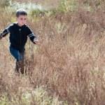 Litle boy runs through the prairie — Stock Photo #7018104
