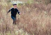 Litle boy runs through the prairie — Stock Photo