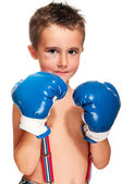 Little bully boy with black eye in boxing gloves wet — Stock Photo