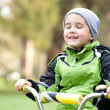 Little boy riding bike outdoors on the meadow with eyes closed - Stock Photo