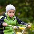 Little boy riding bike outdoors in forest - Stock Photo