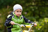 Little boy riding bike outdoors in forest — Stock Photo